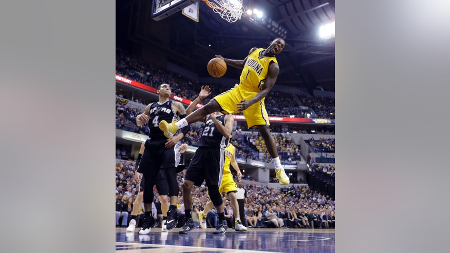 Indiana Pacers guard Lance Stephenson (1) reacts after a slam dunk over San Antonio Spurs guard Danny Green (4) and forward Tim Duncan (21) in the first half of an NBA basketball game in Indianapolis, Monday, March 31, 2014.  (AP Photo/Michael Conroy)