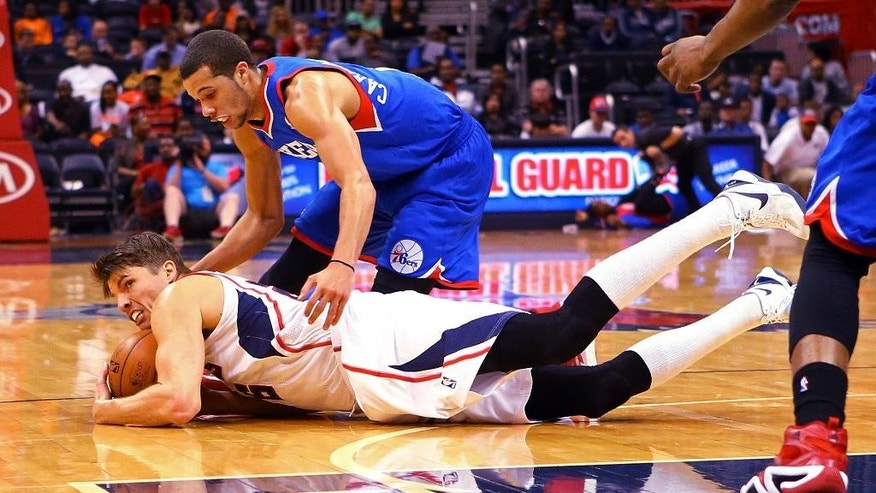 Atlanta Hawks guard Kyle Korver, returning to playing after missing six games with back spasms, dives for a loose ball against 76ers guard Michael Carter-Williams, top, during the second half of an NBA basketball game on Monday, March 31, 2014, in Atlanta.  (AP Photo/Atlanta Journal-Constitution, Curtis Compton)  MARIETTA DAILY OUT; GWINNETT DAILY POST OUT; LOCAL TV OUT; WXIA-TV OUT; WGCL-TV OUT