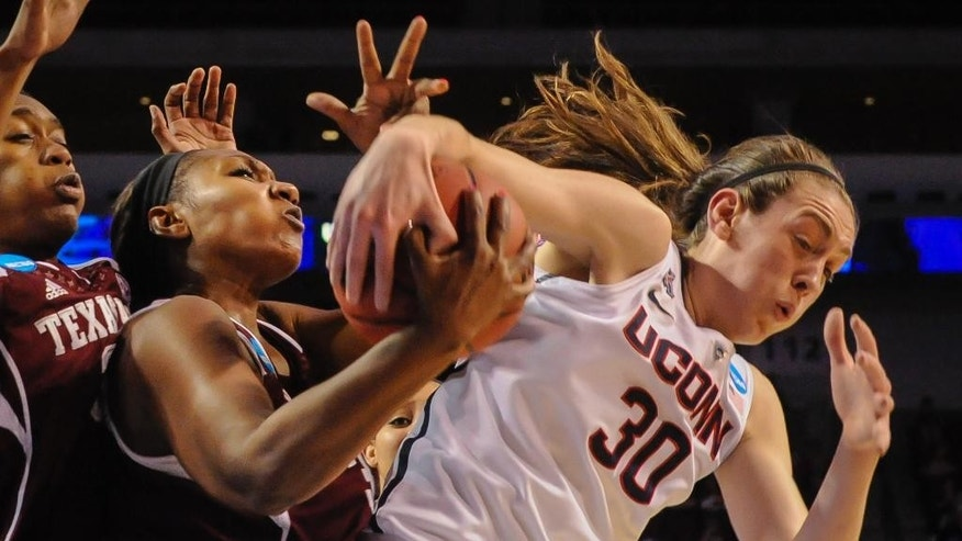 Texas A&M's Karla Gilbert (34) and Connecticut's Breanna Stewart (30) battle for a rebound during the first half of their  regional final in the NCAA college basketball tournament in Lincoln, Neb., Monday March 31, 2014. (AP Photo/Dave Weaver)