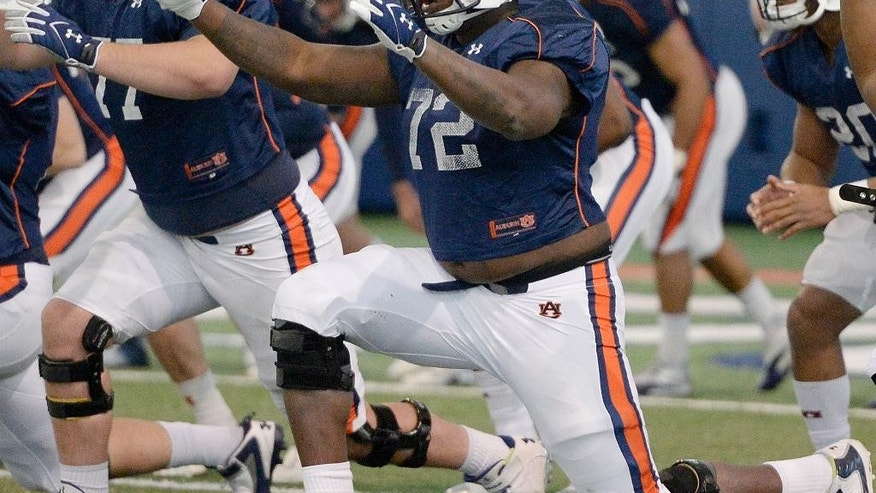 In this March 25, 2014 photo, Auburn offensive linemen Shane Callahan (77) and Shon Coleman (72) stretch during an NCAA college spring football practice at the Auburn Athletic Complex in Auburn, Ala.  Coleman is battling to replace Greg Robinson as the starting left tackle a few years after overcoming a much tougher fight against cancer. (AP Photo/AL.com, Julie Bennett)