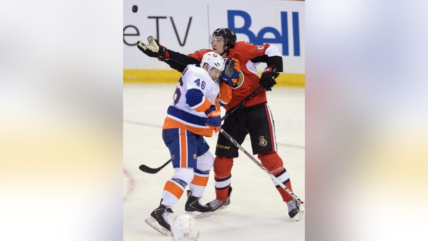 Ottawa Senators' Mark Stone reaches for an airborne puck as New York Islanders' Matt Donovan avoids a hit during the second period of an NHL hockey game in Ottawa, Ontario, on Wednesday, April 2, 2014. (AP Photo/The Canadian Press, Sean Kilpatrick)