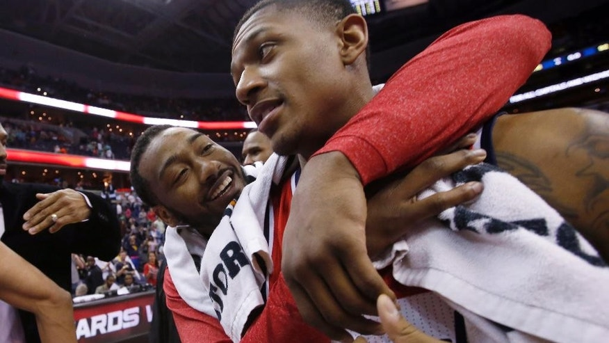 Washington Wizards guards John Wall, left, and Bradley Beal celebrate after an NBA basketball game against the Boston Celtics on Wednesday, April 2, 2014, in Washington. The Wizards won 118-92, and clinched a playoff berth. (AP Photo/Alex Brandon)