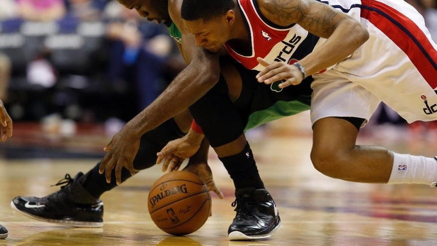 Boston Celtics center Joel Anthony (50) and Washington Wizards guard Bradley Beal, right, go for the ball during the first half of an NBA basketball game Wednesday, April 2, 2014, in Washington. (AP Photo/Alex Brandon)