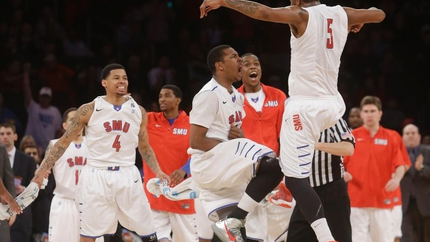 SMU's Markus Kennedy (5) celebrates with Sterling Brown, center, and Keith Frazier (4) after scoring during the second half of an NCAA college basketball game against Clemson in the semifinals of the NIT Tuesday, April 1, 2014, in New York. SMU won the game 65-59. (AP Photo/Frank Franklin II)
