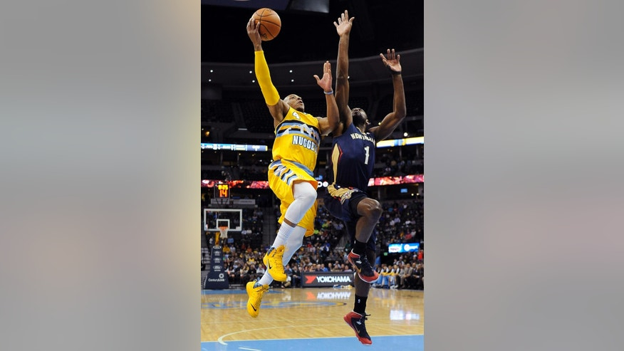 Denver Nuggets guard Randy Foye, left, goes up for a shot over New Orleans Pelicans forward Tyreke Evans, right, in the first half of an NBA basketball game on Wednesday, April 2, 2014, in Denver. (AP Photo/Chris Schneider)