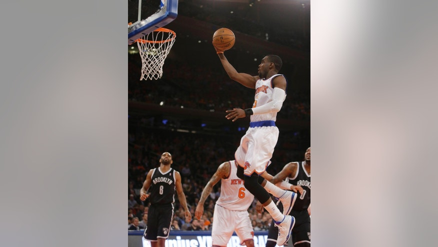 New York Knicks' Tim Hardaway Jr. (5) drives past Brooklyn Nets' Alan Anderson (6) during the first half of an NBA basketball game Wednesday, April 2, 2014, in New York.  (AP Photo/Frank Franklin II)
