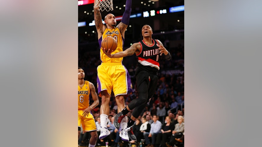 Portland Trail Blazers guard Damian Lillard, right, goes to the basket as Los Angeles Lakers center Robert Sacre defends during the second half of an NBA basketball game in Los Angeles, Tuesday, April 1, 2014. (AP Photo/Danny Moloshok)
