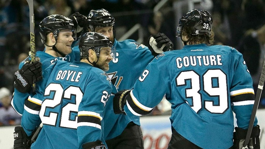 San Jose Sharks defenseman Dan Boyle (22) celebrates his goal with defenseman Matt Irwin, left, and Logan Couture (39) after scoring against the Edmonton Oilers during the first period of an NHL hockey game Tuesday, April 1, 2014, in San Jose, Calif. (AP Photo/Tony Avelar)