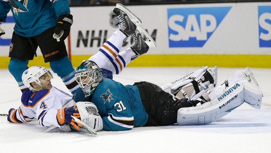 Edmonton Oilers left wing Taylor Hall (4) collides with San Jose Sharks goalie Antti Niemi (31), of Finland, during the second period of an NHL hockey game Tuesday, April 1, 2014, in San Jose, Calif. (AP Photo/Tony Avelar)
