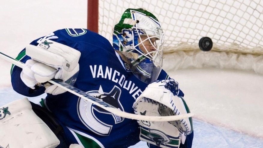 Vancouver Canucks goalie Eddie Lack watches a shot by New York Rangers right wing Martin St. Louis go past him during the third period of an NHL hockey game Tuesday, April 1, 2014, in Vancouver, British Columbia. (AP Photo/The Canadian Press, Jonathan Hayward)