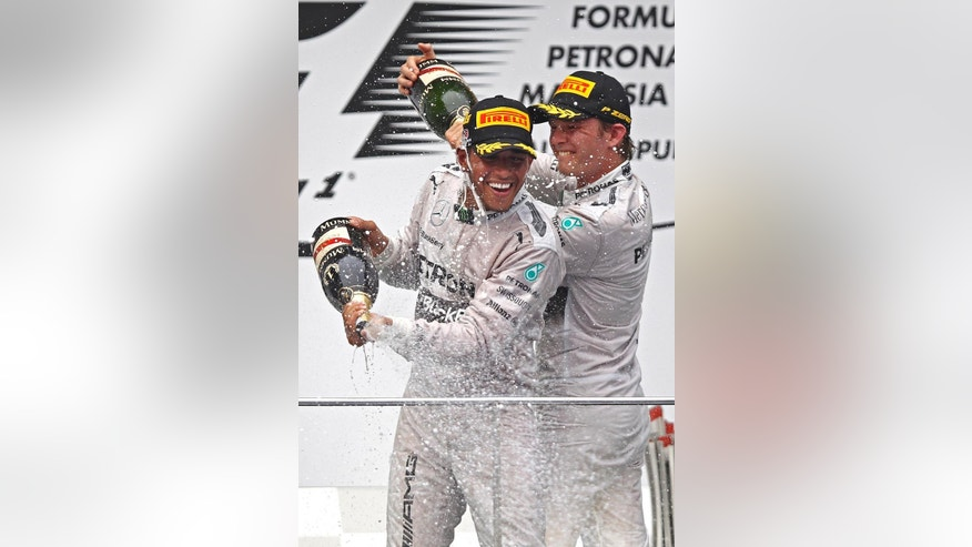 Mercedes driver Lewis Hamilton, left, of Britain and his teammate Nico Rosberg of Germany spray champagnes during the prize presentation on the podium after the Malaysian Formula One Grand Prix at Sepang International Circuit in Sepang, Malaysia, Sunday, March 30, 2014. Hamilton won the race while Rosberg finished in second. (AP Photo/Lai Seng Sin)