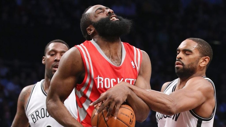 Houston Rockets guard James Harden (13) is fouled by Brooklyn Nets forward Alan Anderson, right, as center Andray Blatche (0) looks on during the second half of their NBA basketball game at the Barclays Center, Tuesday, April 1, 2014, in New York. (AP Photo/John Minchillo)