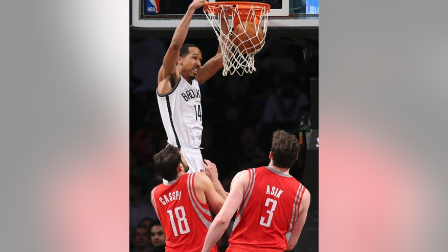 Brooklyn Nets guard Shaun Livingston (14) dunks as Houston Rockets forward Omri Casspi (18) and center Omer Asik (3) look on during the second half of their NBA basketball game at the Barclays Center, Tuesday, April 1, 2014, in New York. (AP Photo/John Minchillo)