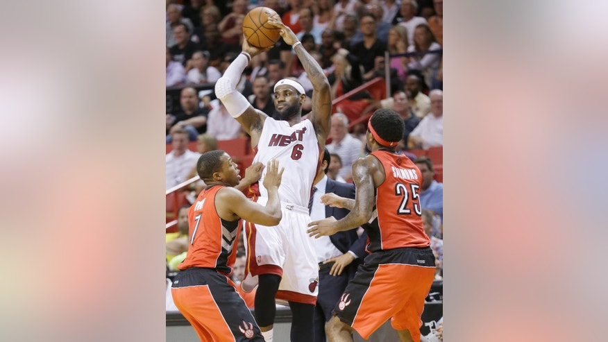 Miami Heat forward LeBron James (6) passes past Toronto Raptors guard Kyle Lowry (7) and forward John Salmons (25) during the first half of an NBA basketball game, Monday, March 31, 2014 in Miami. (AP Photo/Wilfredo Lee)