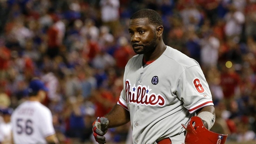 Philadelphia Phillies' Ryan Howard removes his batting helmet after being struck out by Texas Rangers' Neal Cotts (56), leaving two runners on in the eighth inning of a baseball game, Tuesday, April 1, 2014, in Arlington, Texas. The Rangers won 3-2. (AP Photo/Tony Gutierrez)
