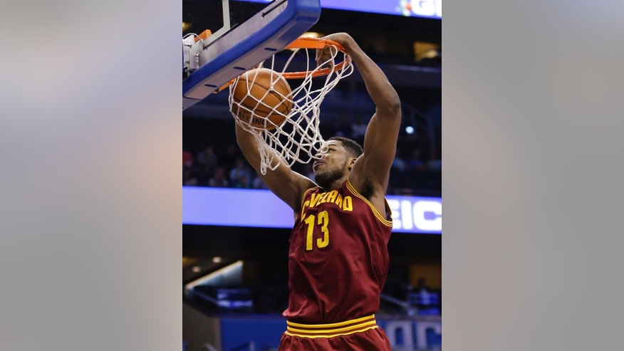 Cleveland Cavaliers' Tristan Thompson (13) makes an uncontested dunk against the Orlando Magic during the first half of an NBA basketball game in Orlando, Fla., Wednesday, April 2, 2014. (AP Photo/John Raoux)