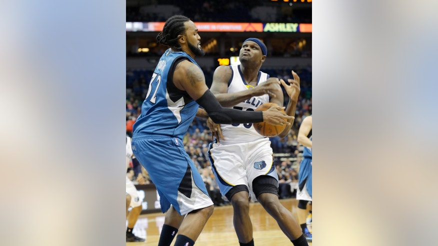 Minnesota Timberwolves center Ronny Turiaf, left, of France, strips the ball from Memphis Grizzlies forward Zach Randolph (50) during the second quarter of an NBA basketball game in Minneapolis, Wednesday, April 2, 2014. (AP Photo/Ann Heisenfelt)
