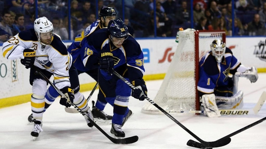 St. Louis Blues' Magnus Paajarvi, of Sweden, reaches for a loose puck as Blues goalie Brian Elliott, right, and Buffalo Sabres' Ville Leino, left, of Finland, watch during the first period of an NHL hockey game on Thursday, April 3, 2014, in St. Louis. (AP Photo/Jeff Roberson)