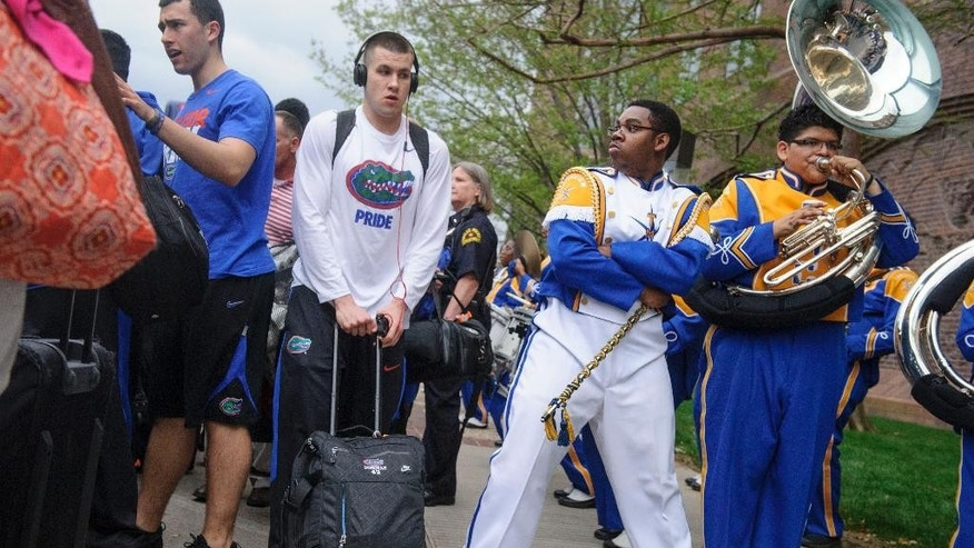 Florida's Billy Donovan, center left, walks past drum major Khyree Henderson, second from right, and the Townview Marching Band outside a hotel in Dallas on Wednesday, April 2, 2014. Florida plays Connecticut on Saturday in the semifinals of the NCAA men's college basketball tournament in Arlington, Texas. (AP Photo/The Dallas Morning News, Matthew Busch) MANDATORY CREDIT; MAGS OUT; TV OUT; INTERNET USE BY AP MEMBERS ONLY; NO SALES