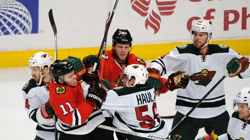 Chicago Blackhawks' Jeremy Morin (11) and Minnesota Wild's Erik Haula (56) get into an altercation in the second period of an NHL hockey game in Chicago, Thursday, April 3, 2014. (AP Photo/David Banks)