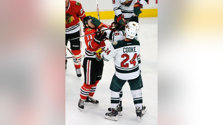 Chicago Blackhawks' Jeremy Morin (11) gets a glove in the face from Minnesota Wild's Erik Haula (56) in the second period of an NHL hockey game in Chicago, Thursday, April 3, 2014. (AP Photo/David Banks)