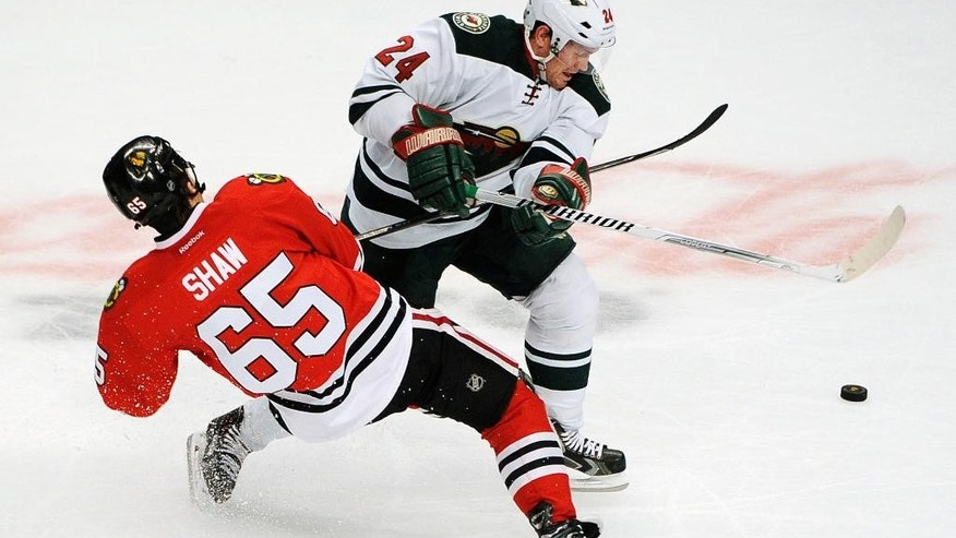 Minnesota Wild's Matt Cooke (24) checks Chicago Blackhawks' Andrew Shaw (65) in the second period of an NHL hockey game in Chicago, Thursday, April 3, 2014. (AP Photo/David Banks)