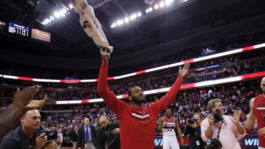 Washington Wizards guard John Wall, center, celebrates after an NBA basketball game against the Boston Celtics on Wednesday, April 2, 2014, in Washington. The Wizards won 118-92, and clinched a playoff berth. (AP Photo/Alex Brandon)