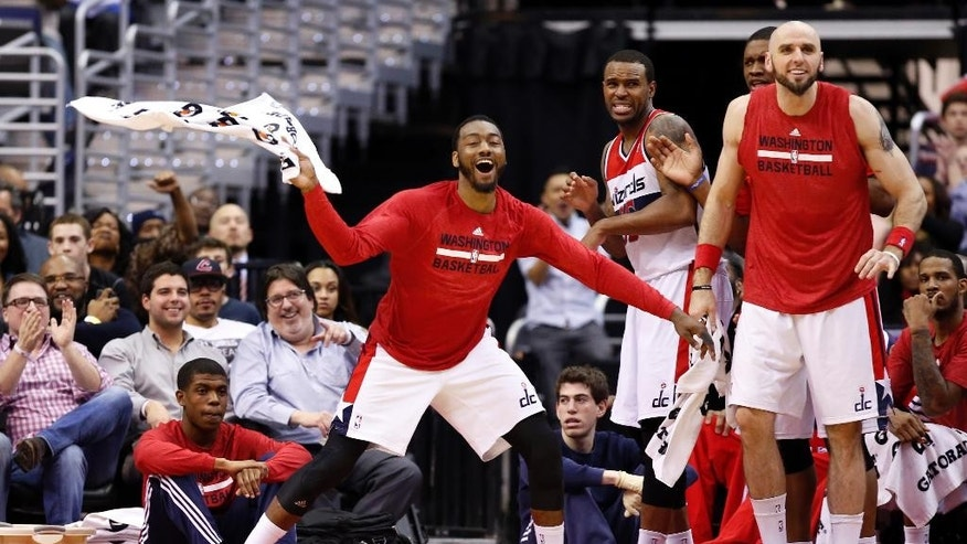 Washington Wizards guard John Wall, left, with forward Trevor Booker and center Marcin Gortat, right, from Poland, celebrate near the bench in the second half of an NBA basketball game against the Boston Celtics on Wednesday, April 2, 2014, in Washington. The Wizards won 118-92, and clinched a playoff berth. (AP Photo/Alex Brandon)
