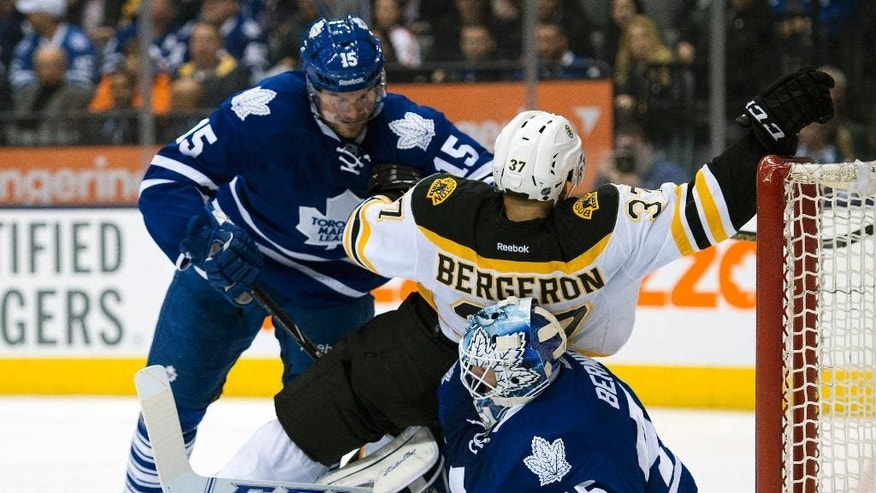 Toronto Maple Leafs defenseman Paul Ranger (15) drives Boston Bruins center Patrice Bergeron onto goaltender Jonathan Bernier during the third period of an NHL hockey game in Toronto on Thursday, April 3, 2014. Bernier left the game injured on the play. (AP Photo/The Canadian Press, Frank Gunn)