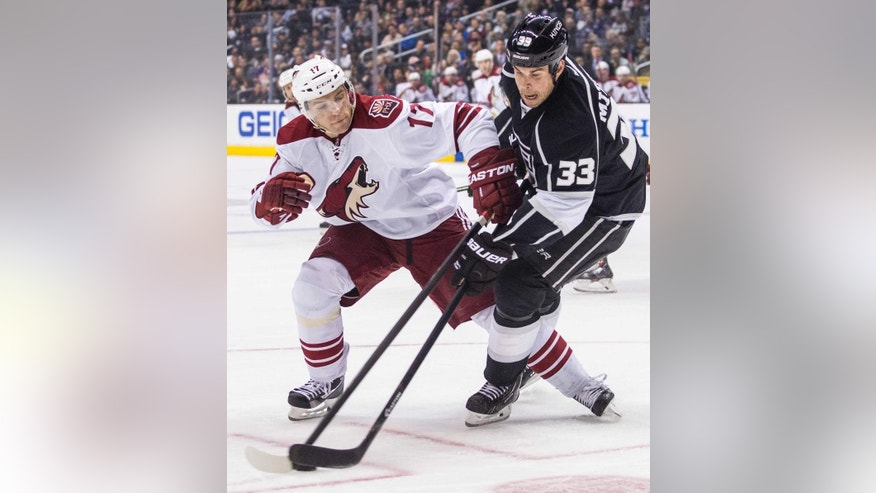 Los Angeles Kings defenseman Willie Mitchell (33) and Phoenix Coyotes forward Radim Vrbate (17), of the Czech Republic, vie for the puck during the first period of an NHL hockey game, Wednesday, April 2, 2014, in Los Angeles. (AP Photo/Ringo H.W. Chiu)