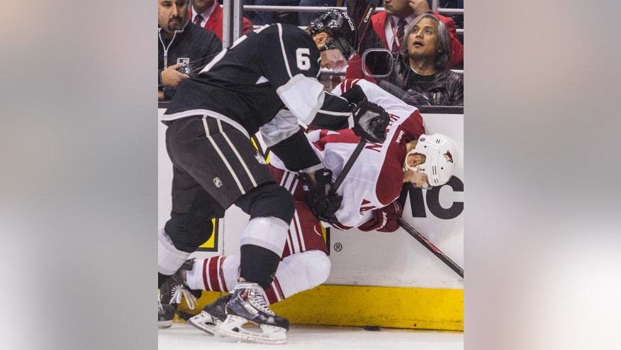 Los Angeles Kings defenseman Jake Muzzin (6) and Phoenix Coyotes forward Jeff Halpern (14) vie for the puck during the first period of an NHL hockey game, Wednesday, April 2, 2014, in Los Angeles.  (AP Photo/Ringo H.W. Chiu)