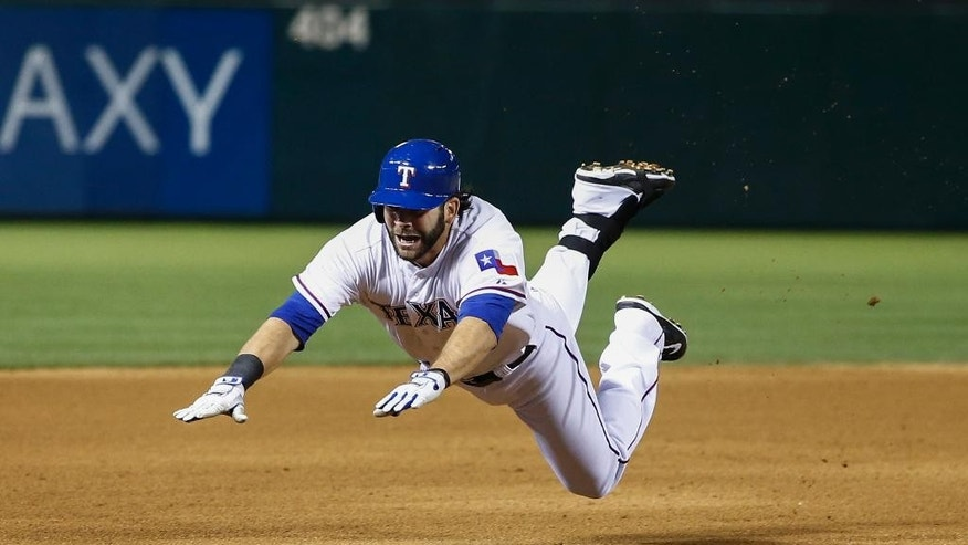 Texas Rangers' Mitch Moreland dives headfirst into third base for a triple against the Philadelphia Phillies during the seventh inning of a baseball game on Wednesday, April 2, 2014, in Arlington, Texas. (AP Photo/Jim Cowsert)
