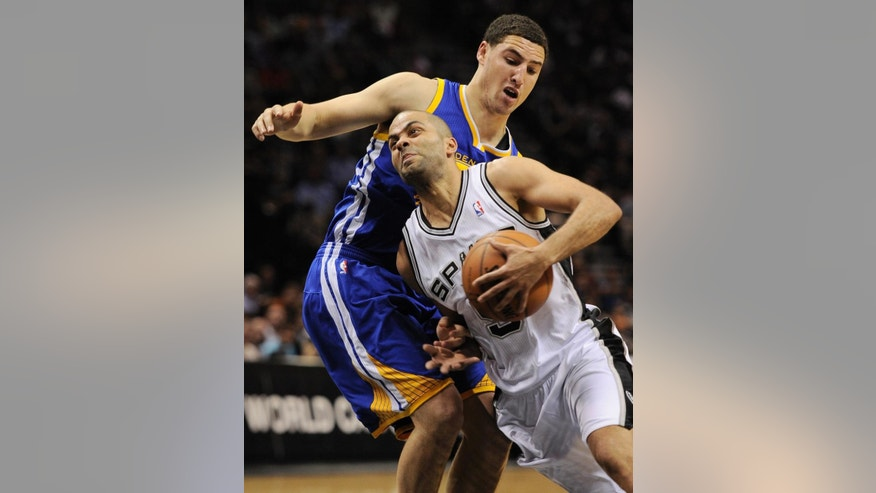 San Antonio Spurs guard Tony Parker, right, of France, drives around Golden State Warriors guard Klay Thompson during the first half of an NBA basketball game on Wednesday, April 2, 2014, in San Antonio. (AP Photo/Darren Abate)