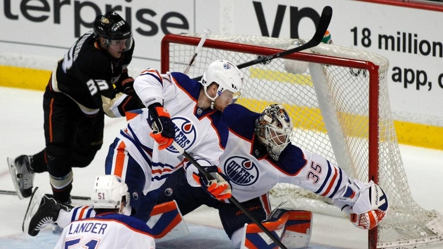 Edmonton Oilers goalie Viktor Fasth (35) and defenseman Anton Belov, center, of Russia, protect the goal from Anaheim Ducks left wing Jakob Silfverberg (33), of Sweden, in the third period of an NHL hockey game Wednesday, April 2, 2014, in Anaheim, Calif. The Ducks won 3-2. (AP Photo/Alex Gallardo)