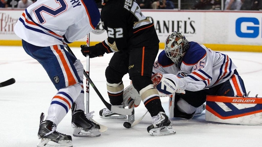 Edmonton Oilers defenseman Jeff Petry (2) and Anaheim Ducks center Mathieu Perreault (22) look for a rebound as goalie Viktor Fasth (35), of Sweden, reaches to sweep away the puck during the second period of an NHL hockey game Wednesday, April 2, 2014, in Anaheim, Calif.(AP Photo/Alex Gallardo)