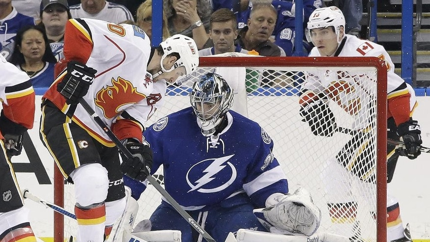 Tampa Bay Lightning goalie Ben Bishop (30) stops a shot by Calgary Flames left wing Curtis Glencross (20) during the second period of an NHL hockey game on Thursday, April 3, 2014, in Tampa, Fla. Flames' Mike Cammalleri (13) looks on. (AP Photo/Chris O'Meara)