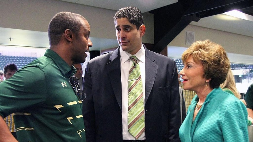 South Florida's new men's basketball coach, Orlando Antigua, center, is congratulated by football coach Willie Taggart and USF President Judy Genshaft on Tuesday, April 1, 2014, in Tampa, Fla., after a news conference to introduce Antigua. (AP Photo/Tampa Tribune, Andy Jones) ST. PETE, LAKELAND, BRADENTON, AND WINTER HAVEN OIUT  MAGS OUT  LOCAL TV OUT: WTSP CH 10, WFTS CH 28, WTVT CH 13, BAYNEWS 9
