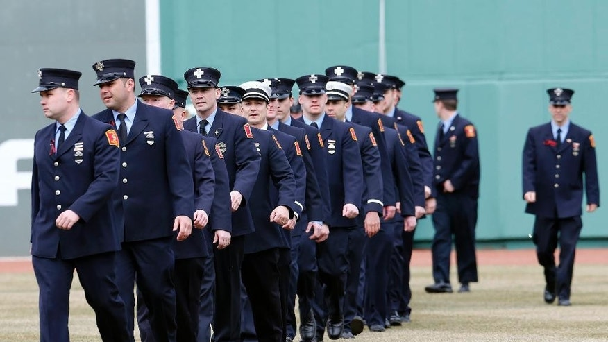 Boston firefighters walk onto the field during pre-game ceremonies before a baseball game between the Boston Red Sox and the Milwaukee Brewers on Opening Day at Fenway Park in Boston, Friday, April 4, 2014. The Red Sox received their 2013 World Series championship rings on Friday during a ceremony that also honored victims of the Boston Marathon bombing and two firefighters who died in a blaze last week. (AP Photo/Michael Dwyer)