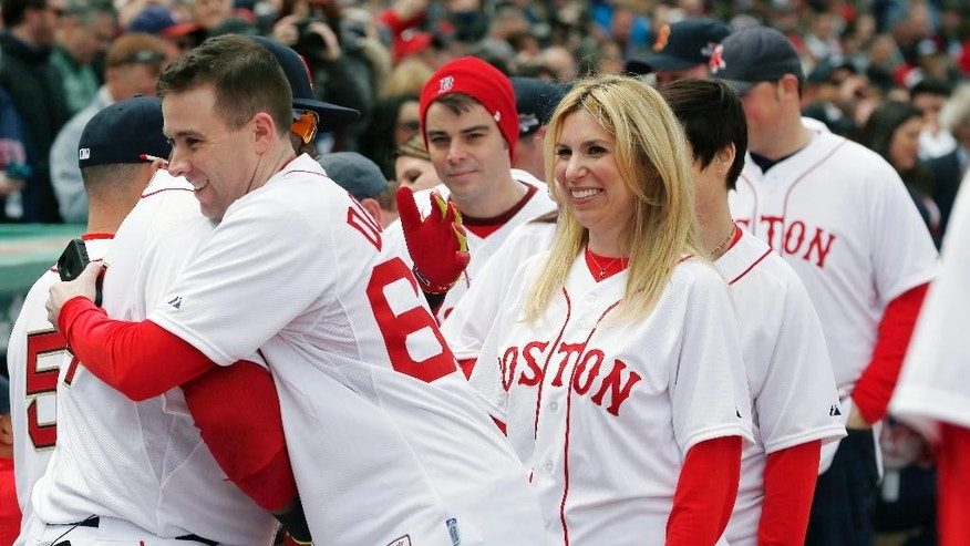 MBTA police officer Richard Donohue, left, hugs Boston Red Sox's David Ortiz as Boston Marathon bombings survivor Heather Abbott, center, stands nearby before the Red Sox's baseball homer-opener against the Milwaukee Brewers at Fenway Park in Boston, Friday, April 4, 2014. (AP Photo/Michael Dwyer)