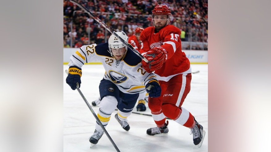 Buffalo Sabres' Johan Larsson (22), of Sweden, races Detroit Red Wings' Riley Sheahan (15) to the puck against the boards during the second period of an NHL hockey game Friday, April 4, 2014, in Detroit. (AP Photo/Duane Burleson)