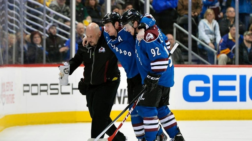 Colorado Avalanche left wing Cody McLeod, center, is helped off the ice by Gabriel Landeskog (92) and a trainer after being injured during the second period of an NHL hockey game against the New York Rangers on Thursday, April 3, 2014, in Denver. (AP Photo/Jack Dempsey)