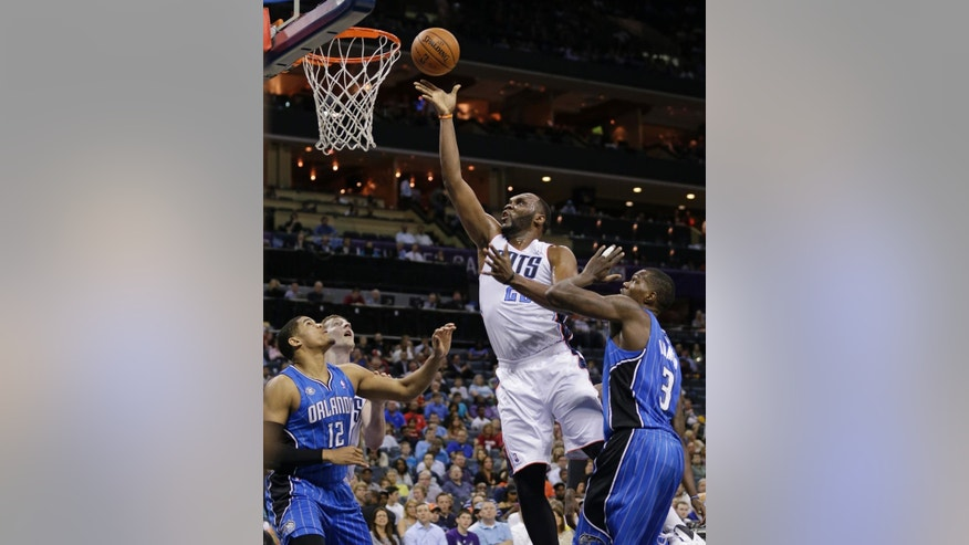 Charlotte Bobcats' Al Jefferson, center, shoots between Orlando Magic's Tobias Harris, left, and Dewayne Dedmon, right, during the first half of an NBA basketball game in Charlotte, N.C., Friday, April 4, 2014. (AP Photo/Chuck Burton)