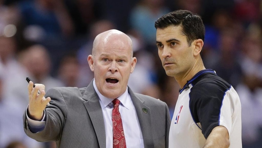 Charlotte Bobcats head coach Steve Clifford, left, complains to referee Tommy Nunez Jr, right, during the first half of an NBA basketball game against the Orlando Magic in Charlotte, N.C., Friday, April 4, 2014. (AP Photo/Chuck Burton)