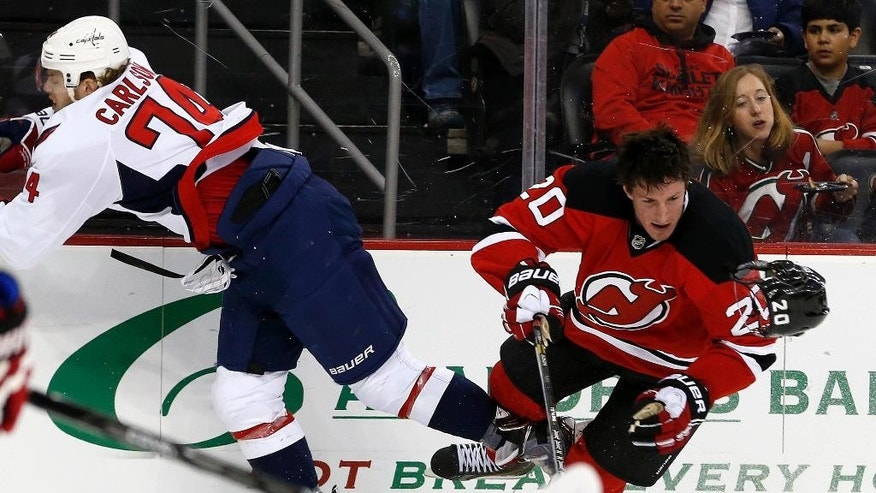 New Jersey Devils center Ryan Carter (20) loses his helmet after colliding with Washington Capitals defenseman John Carlson (74) during the first period of an NHL hockey game, Friday, April 4, 2014, in Newark, N.J. (AP Photo/Julio Cortez)
