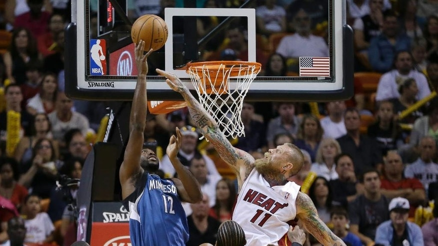Minnesota Timberwolves forward Luc Richard Mbah a Moute (12) goes to the basket as Miami Heat forward Chris Andersen (11) defends during the first half of an NBA basketball game in Miami, Friday, April 4, 2014. (AP Photo/Alan Diaz)
