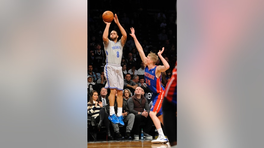 Brooklyn Nets' Deron Williams (8) take aim over Detroit Pistons' Kyle Singler (25) in the first half of an NBA basketball game on Friday, April 4, 2014, in New York. (AP Photo/Kathy Kmonicek)
