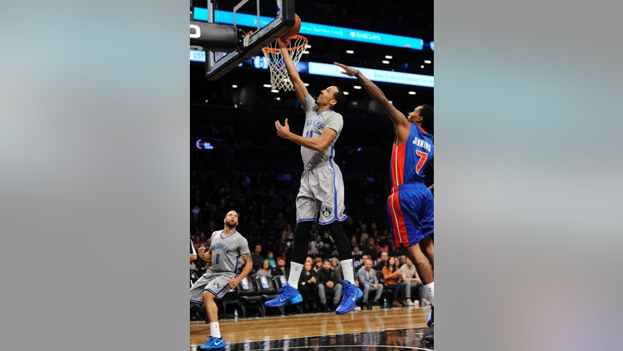 Brooklyn Nets' Deron Williams (8) watches as Shaun Livingston (14) drives the ball to the basket ahead of Detroit Pistons' Brandon Jennings (7) during the first half of an NBA basketball game Friday, April 4, 2014, in New York. (AP Photo/Kathy Kmonicek)
