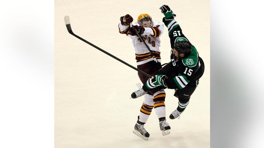 ADVANCE FOR WEEKEND EDITIONS, APRIL 5-6 - FILE - In this Jan. 19, 2013 file photo, Minnesota's Tom Serratore, left, checks North Dakota's Michael Parks off the puck during the first period at Mariucci Arena in Minneapolis,  Minn. For the first time in 67 years, the two teams didn't play in the regular season. It didn't take long for the rivalry to be renewed. They'll meet at the Frozen Four in one of the national semifinal games in Philadelphia on April 10. (AP Photo/The Star Tribune, Kyndell Harkness, File)  ST. PAUL PIONEER PRESS OUT. SOFT OUT MINNEAPOLIS-AREA TV NOT TV, MAGS OUT.