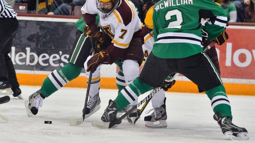 ADVANCE FOR WEEKEND EDITIONS, APRIL 5-6 - FILE - In this Jan. 18, 2013 file photo, Minnesota's Kyle Rau (7) works for the puck against North Dakota's Andrew MacWilliam in the first period of a college hockey game in Minneapolis. For the first time in 67 years, the two teams didn't play in the regular season. It didn't take long for the rivalry to be renewed. They'll meet at the Frozen Four in one of the national semifinal games in Philadelphia on April 10. (AP Photo/Bre McGee, File)