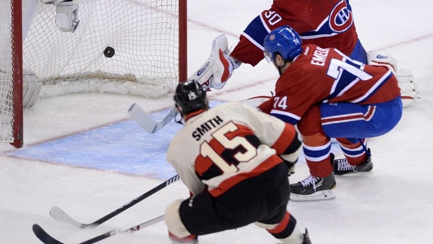 CORRECTS DATE TO FRIDAY APRIL 4 - Ottawa Senators forward Zack Smith (15) blasts the puck past Montreal Canadiens goalie Peter Budaj and defenseman Alexei Emelin during first period NHL hockey action in Ottawa on Friday, April 4, 2014. (AP Photo/The Canadian Press, Sean Kilpatrick)